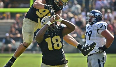 Purdue's Evan Panfil, top, and Eddy Wilson celebrate after Wilson sacked Nevada quarterback Tyler Stewart during an NCAA football game Saturday Sept. 24, 2016, in West Lafayette, Ind. Purdue defeated Nevada 24-14. (Frank Oliver/Journal & Courier via AP)