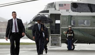 President Barack Obama walks from Marine One in the rain to board Air Force One at Richmond International Airport, in Richmond, Va., Wednesday, Sept. 28, 2016, en route to Washington. (AP Photo/Carolyn Kaster)