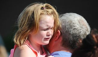 Lilly Chapman, 8, cries after being reunited with her father, John Chapman at Oakdale Baptist Church on Wednesday, Sept. 28, 2016, in Townville, S.C. Students were evacuated to the church following a shooting at Townville Elementary School. A teenager opened fire at a South Carolina elementary school on Wednesday. (AP Photo/Rainier Ehrhardt)