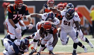 FILE - In this Sunday, Sept. 25, 2016, file photo, Cincinnati Bengals running back Jeremy Hill (32) runs the ball as Denver Broncos nose tackle Sylvester Williams (92), defensive end Derek Wolfe (95), and inside linebacker Todd Davis (51) close in during the first half of an NFL football game in Cincinnati. Even with some work to do on. plugging rushing lanes and escape routes, the Denver Broncos remain the gold standard of defenses in the NFL. (AP Photo/Gary Landers, File)