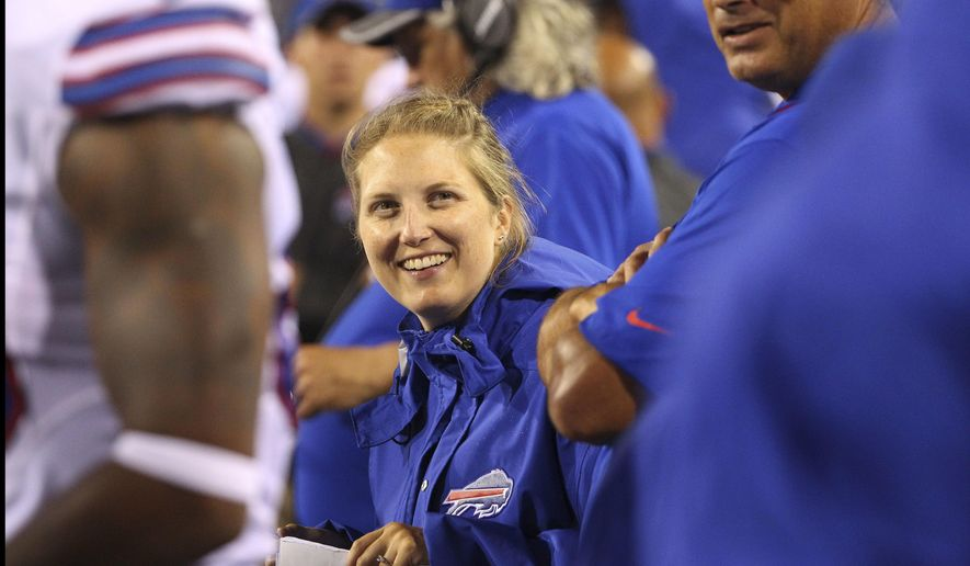FILE - In this Aug. 13, 2016, file photo, Buffalo Bills special teams and quality control coach Kathryn Smith works from the sideline during the second half of a preseason NFL football game against the Indianapolis Colts in Orchard Park, N.Y.  In its report released Wednesday, Sept. 28,2 016, The Institute for Diversity and Ethics in Sport gave the NFL its seventh consecutive A on racial hiring practices and a combined grade of B for hiring minorities and women. Dr. Richard Lapchick, the director of the institute, is the primary author of the report card that independently evaluates the NFL's racial and gender hiring practices at both league and team levels, (AP Photo/Bill Wippert, File)