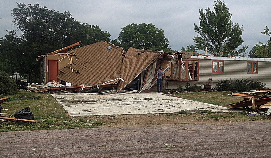 In this Monday, Sept. 5, 2016 photo, a man views a severely damaged home in Springfield, S.D.  Springfield residents are still dealing with the aftermath of a storm early this month that damaged or destroyed dozens of homes and displaced scores of people.  (Shauna Marlette/Yankton Press & Dakotan via AP)
