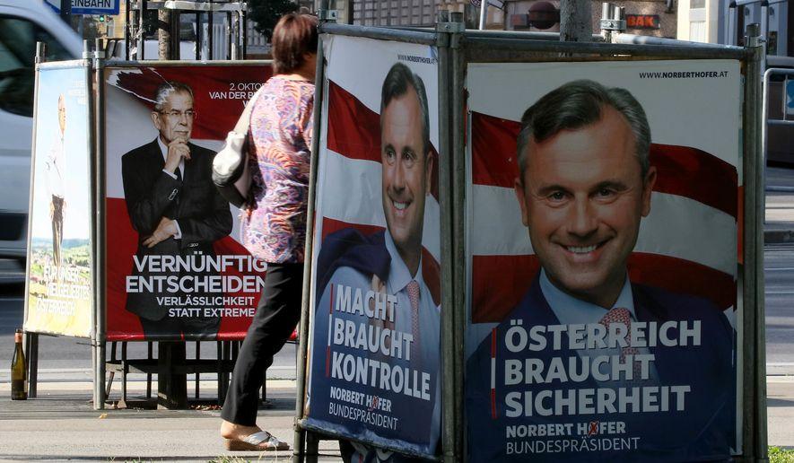 People walk between election posters of Alexander Van der Bellen and Norbert Hofer in Vienna on Sept. 12. (Associated Press)