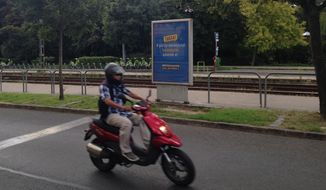"In this Aug. 13, 2016, file picture a person on motorbike passes a government poster promoting the Oct. 2 referendum against any EU quotas to resettle migrants. reading ""Did you know?"" Hungarians will vote Sunday in a referendum called by Prime Minister Viktor Orbans government, seeking political support against any future plans by the European Union to resettle refugees or asylum seekers among members of the bloc. (AP Photo/ Pablo Gorondi, file)"