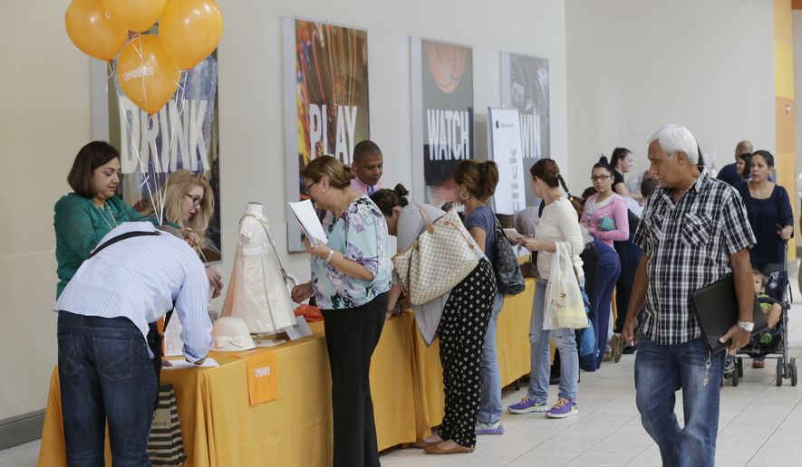 In this Tuesday, Oct. 6, 2015, file photo, job applicants fill out forms during a job fair at Dolphin Mall in Miami. (AP Photo/Wilfredo Lee, File)