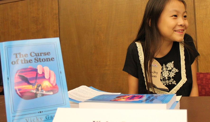 "ADVANCE FOR MONDAY OCT. 3 AND THEREAFTER - In a Sept. 20, 2016 photo, author Vicky Gao, 11, smilesat all of the authors during the Abilene Author Showcase at the downtown Abilene Public Library as part of this year's West Texas Book Festival. Vicky is 11. Her latest book is ""The Curse of the Stone."" It's 245 pages and self-published. (Greg Jaklewicz/Reporter-News via AP)"