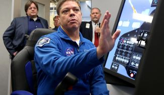 NASA astronaut Bob Behnken explains an ascent simulation on one of Boeing's CST-100 Starliner training simulators at the Johnson Space Center in Houston on Wednesday, Sept. 28, 2016. (Jennifer Reynolds/The Galveston County Daily News via AP)