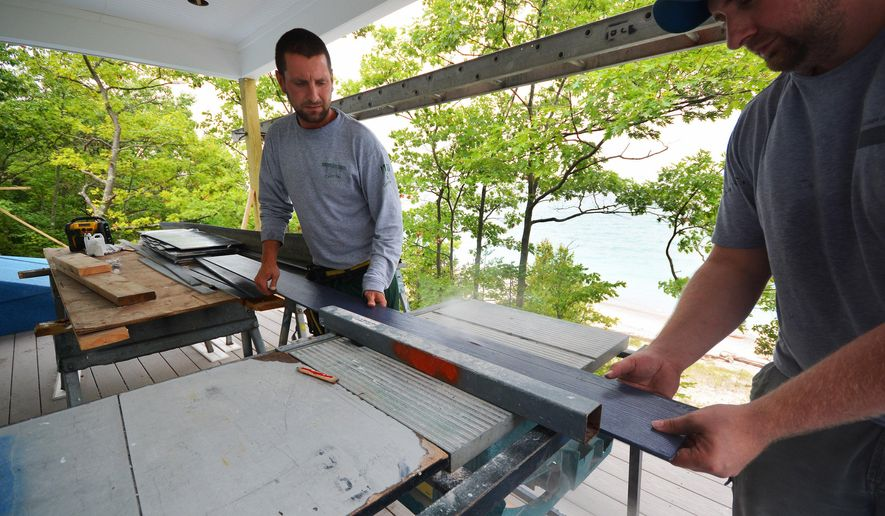 In this Sept. 8, 2016 photo, Andy Desmond, left, helps trim a piece of siding on a house being built north of Frankfort, Mich., just steps from a Lake Michigan beach. (Dan Nielsen/Traverse City Record-Eagle via AP)