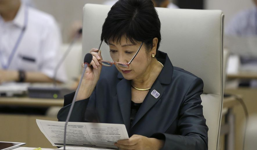 Tokyo Gov. Yuriko Koike looks over a report during an expert panel at the Tokyo Metropolitan government office in Tokyo Thursday, Sept. 29, 2016. The panel, launched by Koike raised concerns about ever-growing unofficial cost estimates and burden on the city and its taxpayers, warned that total cost for the Tokyo 2020 Olympic could exceed 3 trillion yen ($30 billion) unless they take drastic cost-cutting measures. (AP Photo/Shizuo Kambayashi)