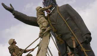 FILE - In this file photo taken Wednesday, April 9, 2003, an Iraqi man, bottom right, watches Cpl. Edward Chin of the 3rd Battalion, 4th Marines Regiment, cover the face of a statue of Saddam Hussein with an American flag before toppling the statue in downtown in Baghdad, Iraq. A bill passed by Congress allowing the families of 9/11 victims to sue the Saudi government has reinforced to some in the Arab world a long-held view that the U.S. only demands justice for its own victims of terrorism, despite decades of controversial U.S. interventions around the world. (AP Photo/Jerome Delay, File)