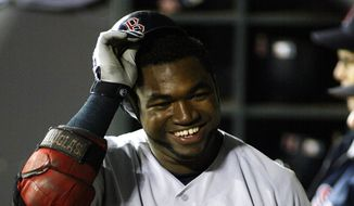 In this Sept. 10, 2004, file photo, Boston Red Sox designated hitter David Ortiz smiles in the dugout after hitting a solo home run against the Seattle Mariners in the sixth inning of a baseball game at Safeco Field in Seattle. Ortiz transformed the Boston Red Sox from a cursed franchise to a three-time World Series champion. (AP Photo/Ted S. Warren, File)