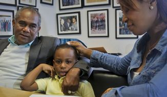 Raphael and Maribel Martinez comfort their son Andy after a press conference at their lawyer's office, Friday Sept. 30, 2016, in New York.  Maribel Martinez has filed a lawsuit against JetBlue Airways for mixing up Andy with another boy and flying him to the wrong city.  (AP Photo/Bebeto Matthews)
