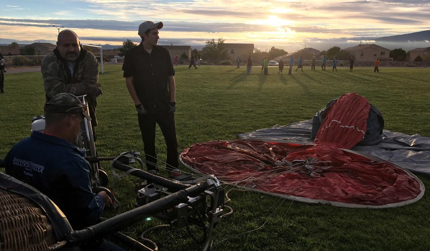 """Stacy Eldridge, left on the ground, prepares to inflate his hot air balloon the """"Redneck Cowboy"""" at Vista Grande Elementary School in Rio Rancho, N.M. on Friday, Sept. 30, 2016, as part of the Albuquerque Aloft program that lifts balloons on school grounds as part of the 45th Albuquerque International Balloon Fiesta. The balloon fiesta is set to begin Saturday and will feature 108 special-shaped balloons representing nine countries. The event ends Oct. 9. (AP Photo/Russell Contreras)"""