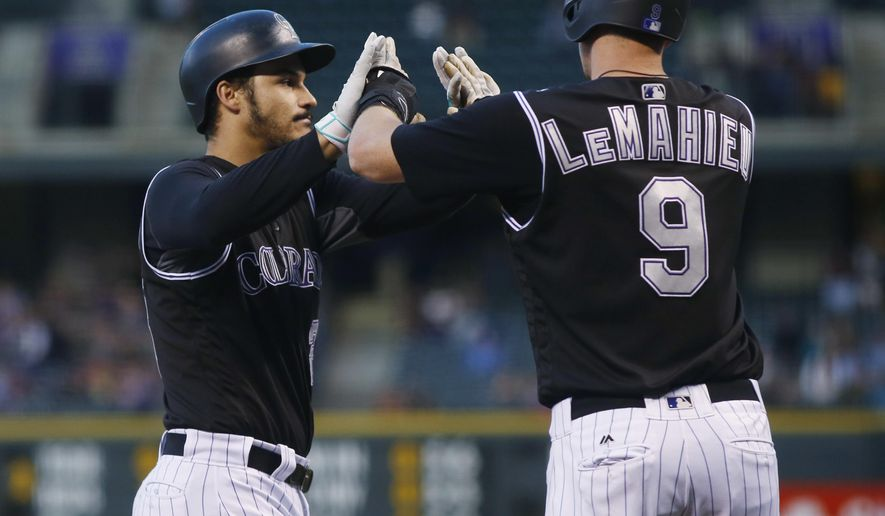 Colorado Rockies' Nolan Arenado, left, is congratulated by DJ LeMahieu as Arenado crosses home plate after hitting a two-run home run off Milwaukee Brewers starting pitcher Brent Suter during the first inning of a baseball game Friday, Sept. 30, 2016, in Denver. (AP Photo/David Zalubowski)