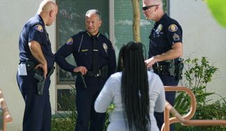 Pasadena Police Chief Phillip L. Sanchez, center, listens to officers as Los Angeles County homicide detectives investigate the death of a black man in Pasadena, Calif., on Friday, Sept. 30, 2016. A witness says it occurred after a struggle with police. A sheriff's statement says the death of the unidentified man occurred about 2 a.m. Friday but gives no details.  (AP Photo/Richard Vogel)