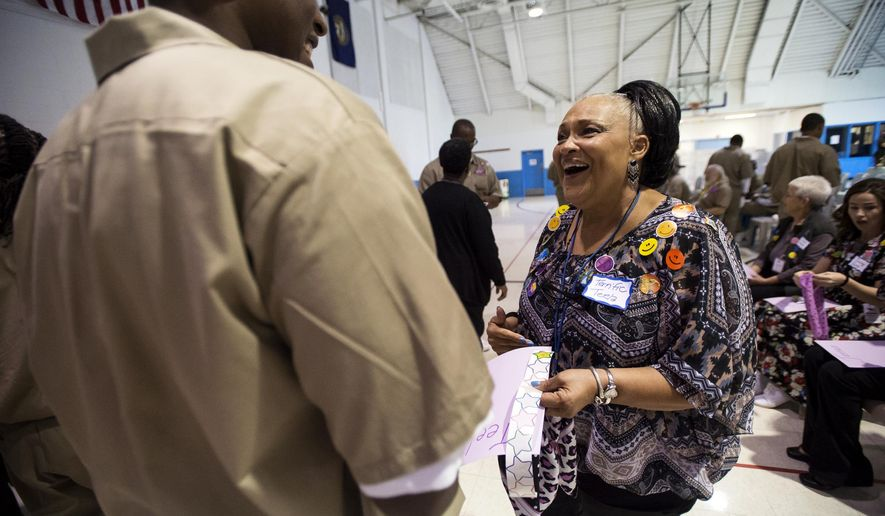 Volunteer Teela Mickles earns a sticker from inmate Andre Johnson after finding something in common during a meet-and-greet exercise on the introductory day of the Defy Ventures program on Thursday, Sept. 29, 2016, at the Nebraska State Penitentiary in Lincoln. The new program is teaching Nebraska convicts how to become entrepreneurs and wage-earners upon their release from prison. The Defy Ventures program currently trains about 1,600 inmates in California and New York.  (Kristin Streff/The Journal-Star via AP)