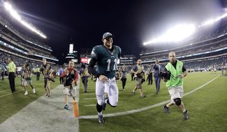 FILE - In this Sept. 25, 2016, file photo, Philadelphia Eagles' Carson Wentz runs off the field after their 34-3 win in an NFL football game against the Pittsburgh Steelers in Philadelphia. Wentz and the unbeaten Eagles were the surprise story in the NFL's first month. The hard part now is ignoring the hype. Before players scattered for rest and relaxation during their bye week, coach Doug Pederson cautioned his team about complacency. (AP Photo/Michael Perez, File)
