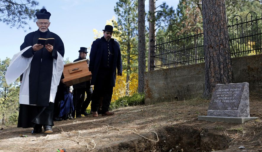Rev. Michael Johnson leads a funeral processional Thursday, Sept. 29, 2016 at Mt. Moriah Cemetery in Deadwood S.D. for the remains of a unknown pioneer from the 1800's, who's body was found in 2012. (Chris Huber/Rapid City Journal via AP)