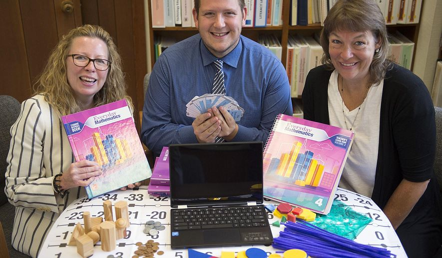 ADVANCE FOR SATURDAY OCT. 1 AND THEREAFTER - JIn an Aug. 18, 2016 photo, Pennsbury officials, from left, Dr. Donna Dunar, Assistant Superintendent, Gary McManus, Math Supervisor K-12, and Kim Walter, Math Specialist, Quarry Hill Elementary, pose with products from their new math program they will use, Everyday Mathematics from McGraw Hill, at the Pennsbury administration offices, in Falls Township, Pa. The Pennsbury School District invested almost $620,000 earlier this year in new textbooks and online teaching tools that are aligned with the state's goals and expectations for what students should be able to do at each grade level in math, English language arts and other core subjects in K-12 public schools. (Joan Hellyer/Bucks County Courier Times via AP)