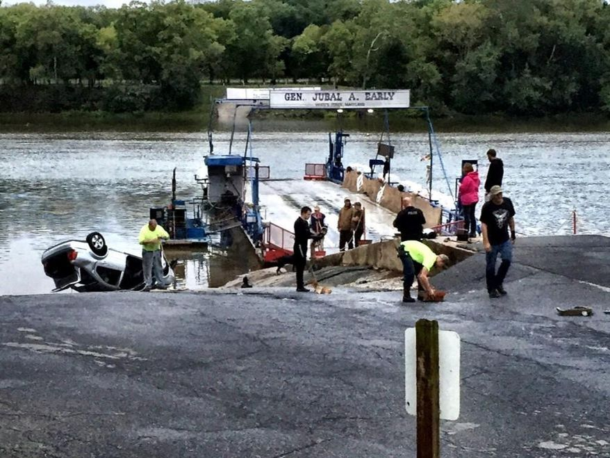 Emergency personnel respond to White's Ferry in Dickerson, Md., after what authorities say a man driving under the influence, drove his car off a ferry into the Potomac River. The driver was rescued, then charged with DUI.  (Neal Augenstein/WTOP via AP)