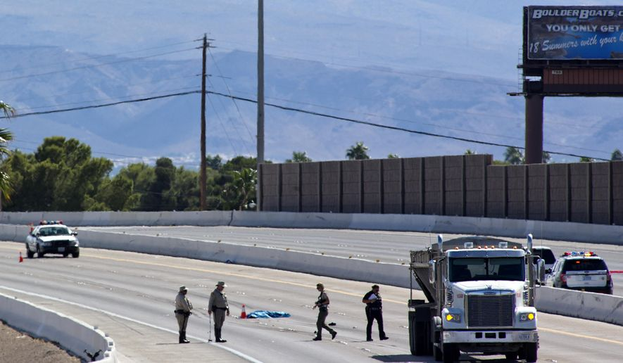 Las Vegas Metro Police investigate a fatal accident on Highway 95 northbound near the Boulder Highway exit in Las Vegas Thursday, Sept. 29, 2016. A man sought for questioning by police in a shooting case that left a man wounded last week was struck and killed Thursday by a tractor-trailer when he tried to run across a Las Vegas freeway, police said. (Steve Marcus/Las Vegas Sun via AP)