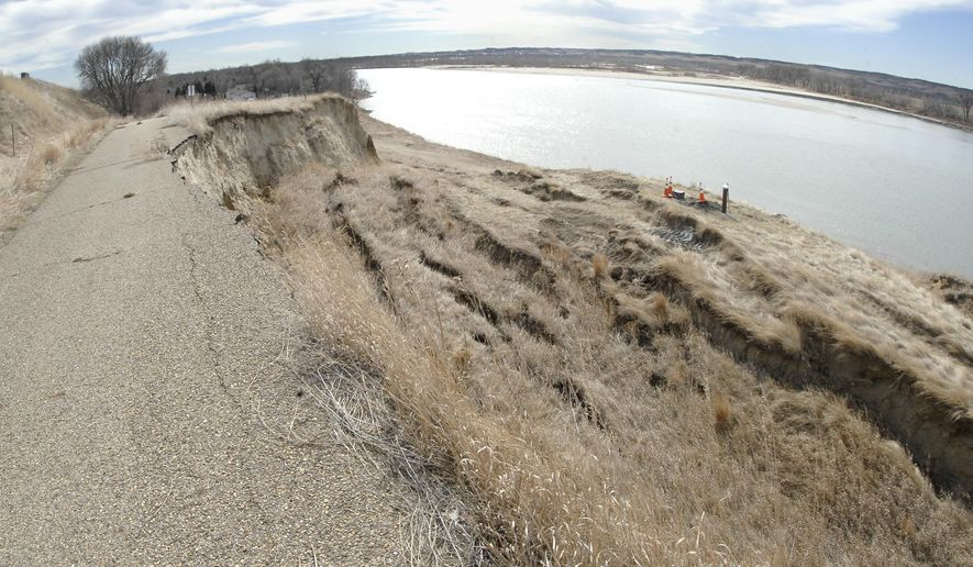 In this March 11, 2016, photo, the bank erosion from the Missouri River at Double Ditch Indian Village, northwest of Bismarck, N.D., on Highway 1804, has expanded to damage a walking path and burial grounds. The process needed to obtain a federal permit for a project to alleviate erosion of native burial grounds at the Double Ditch Indian Village State Historic Site might delay construction until spring. A state historic preservation official says that would be concerning. (Mike McCleary/The Bismarck Tribune via AP)