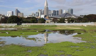 """FILE - In this Nov. 16, 2015, file photo, a skyscraper reflects in a pool of water in the site of Japan's National Stadium demolished for the renovation for the 2020 Olympic games as the compound is shown to the media for the first time after the completion of the demolition work in Tokyo. The price tag of the 2020 Tokyo Olympics could exceed 3 trillion yen ($30 billion) unless drastic cost-cutting measures are taken and several key venues are relocated, an expert panel warned Thursday, Sept. 30, 2016, in the latest blow to Japanese organizers. """"Naturally, anyone who hears these numbers is alarmed,"""" panel leader Shinichi Ueyama said. (AP Photo/Koji Sasahara, File)"""