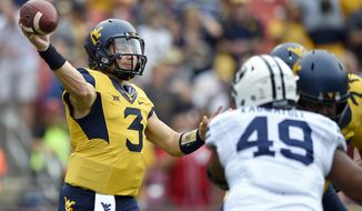FILE - In this Sept. 24, 2016, file photo, West Virginia quarterback Skyler Howard (3) passes while pressured by BYU defensive lineman Moses Kaumatule (49) during the first half of an NCAA college football game Landover, Md. The Mountaineers host Kansas State on Saturday. (AP Photo/Nick Wass, File)