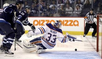 Edmonton Oilers goaltender Cam Talbot (33) reaches back to stop the puck during the second period of an NHL hockey preseason game against the Winnipeg Jets on Friday, Sept. 30, 2016, in Winnipeg, Manitoba. (Trevor Hagan/The Canadian Press via AP)