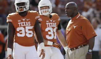 FILE - In this Sept. 10, 2016, file photo, Texas coach Charlie Strong, right, watches his players warm up for an NCAA college football game against UTEP in Austin, Texas. Texas takes on Oklahoma State on Saturday. (AP Photo/Eric Gay, File)