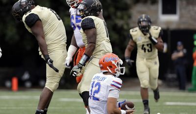 Vanderbilt defensive lineman Adam Butler, left, celebrates after sacking Florida quarterback Austin Appleby (12) for a loss of 8 yards in the first half of an NCAA college football game Saturday, Oct. 1, 2016, in Nashville, Tenn. (AP Photo/Mark Humphrey)