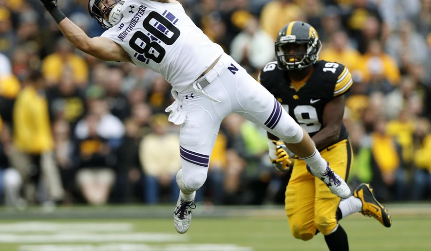 Northwestern wide receiver Austin Carr (80) catches a pass in front of Iowa defensive back Miles Taylor (19) during the second half of an NCAA college football game, Saturday, Oct. 1, 2016, in Iowa City, Iowa. Northwestern won 38-31. (AP Photo/Charlie Neibergall)