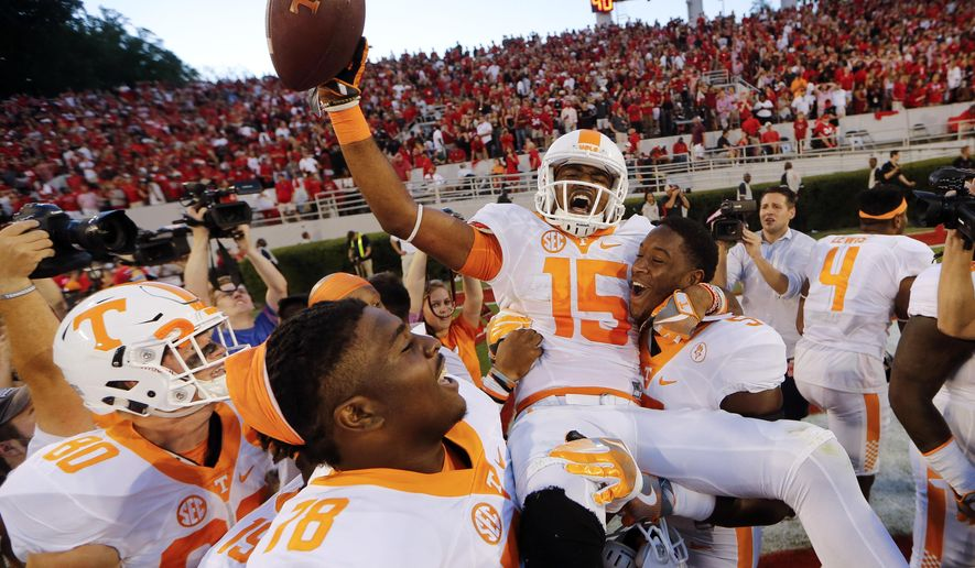 Tennessee wide receiver Jauan Jennings (15) is carried by teammates Kyle Phillips (5) and Charles Mosley (78) after making a last-second touchdown catch to defeat Georgia 34-31 in an NCAA college football game Saturday, Oct. 1, 2016, in Athens, Ga. (AP Photo/John Bazemore)