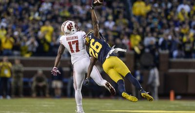 Michigan's cornerback Jourdan Lewis (26) intercepts a pass intended for Wisconsin wide receiver George Rushing in the fourth quarter of an NCAA football game at the Michigan Stadium, Saturday, Oct. 1, 2016, in Ann Arbor, Mich. (Junfu Han/The Ann Arbor News via AP)