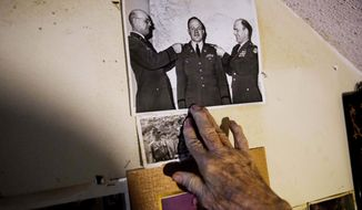 Memorabilia decorates a wall in the home of Frank Gleason, 96, a retired colonel with the Office of Strategic Services, in Atlanta, Wednesday, Sept. 28, 2016. Legislation to recognize the contributions of a group of World War II spies is hung up in Congress. Some 75 years ago, the OSS carried out missions behind enemy lines in Nazi Germany and the Pacific theatre. Gleason's group was tasked with halting the Japanese advance into China. Gleason and his comrades did this by detonating bridges, railroad tracks and anything else. 'We just blew stuff up left and right,' said Gleason. (AP Photo/David Goldman)