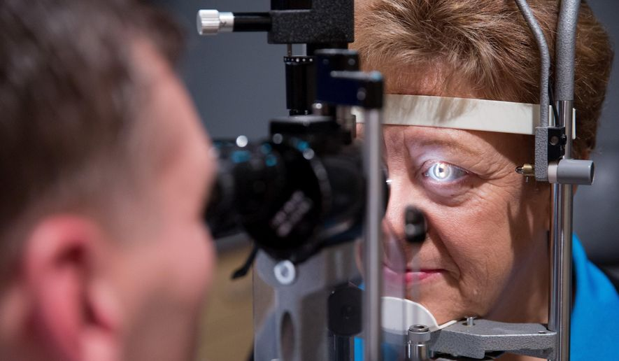 In this Friday, Sept. 16, 2016 photo, Dr. Lance Kugler examines Cheryl Henry's left eye during a follow-up visit at Kugler Vision in Omaha, Neb. (Rebecca Gratz /Omaha World-Herald via AP) **FILE**