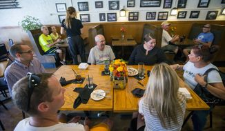 In this Aug. 15, 2016 photo, Katie Harvey-Martinez, seated right center, talks with lunchtime patrons and friends at Harvey's Diner & Pub (formally Dexfield Diner) which she recently opened with her husband Rick, in Redfield, Iowa. (Rodney White  /The Des Moines Register via AP  )