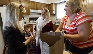 ADVANCE FOR WEEKEND EDITIONS OCT. 1-2 - In this Tuesday, Sept. 27, 2016 photo, Yazidi refugee Fadheela Mhmdah, center, and her son Amad, 3, graciously unpack groceries brought by co-sponsors Jillian Jenkins, left, and Sara Gillian at their new apartment in north Lincoln, Neb. (Kristen Streff/The Journal-Star via AP)
