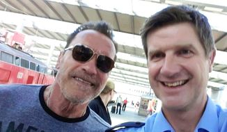 In this Oct.1, 2016 photo provided by the Munich police former Californian state governor Arnold Schwarzenegger poses with police officer Stefan Schmitt for a selfie in the main train station in Munich, Germany. Schwarzenegger's bodyguard was stopped when cycling with Schwarzenegger too fast through the train station. As an apologize Schwarzenegger offered a selfie. (Stefan Schmitt/Munich police via AP)