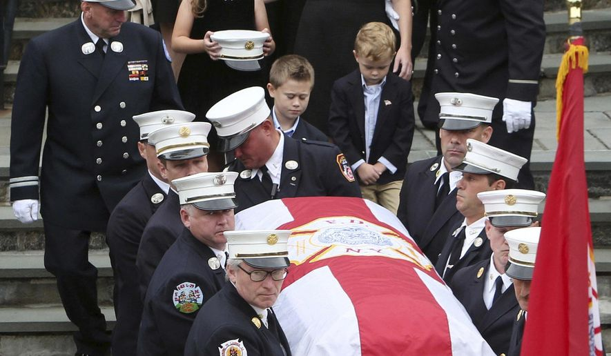 As his family follows behind, pallbearers carry the casket of New York Fire Department Battalion Chief Michael Fahy at Annunciation Church in Yonkers, N.Y., on Saturday, Oct. 1, 2016. Fahy died while fighting a fire at suspected marijuana grow house in the Bronx borough of New York on Thursday, Sept. 27, 2016. (Frank Becerra Jr./The Journal News via AP)