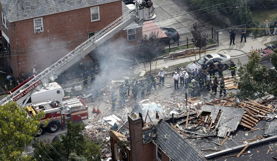 FILE - In this Sept. 27, 2016 file photo, emergency service personnel work at the scene of a house explosion in the Bronx borough of New York.   The  explosion that destroyed a New York City house and killed a firefighter has drawn attention to marijuana-making methods that are legal in some states _ but can also be lethal. Authorities are investigating whether the people who set up an indoor marijuana farm in the house tampered with gas lines or mishandled other materials in ways that caused the explosion.(AP Photo/Mary Altaffer)