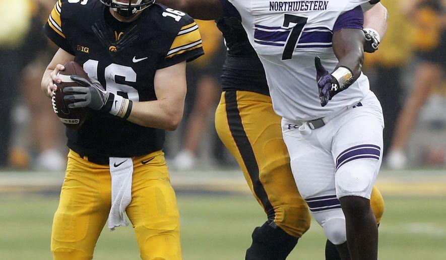 Iowa quarterback C.J. Beathard (16) runs from Northwestern defensive lineman Ifeadi Odenigbo (7) during the second half of an NCAA college football game, Saturday, Oct. 1, 2016, in Iowa City, Iowa. Northwestern won 38-31. (AP Photo/Charlie Neibergall)