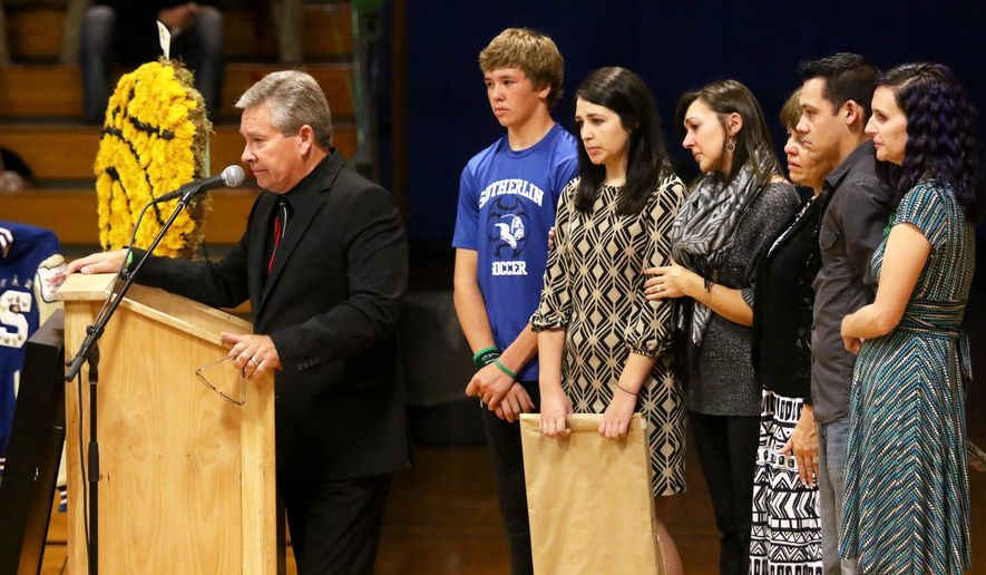In this Oct. 17, 2015, Randy Scroggins, pastor of the New Beginnings church in Roseburg, Ore., speaks at Treven Anspach's memorial service at Sutherlin High School on Oct. 17, 2015, in Sutherlin, Ore. Standing behind Scroggins, from left, Jeremiah Scroggins, Lacey Scroggins, Amanda Field, Randy's wife, Lisa Scroggins, Andrew Katter and Ashley Katter. Lacey Scroggins, an 18-year-old freshman student back on Oct. 1, 2015, was one of the survivors of a shooting in a Snyder Hall classroom at Umpqua Community College. (Michael Sullivan/The News-Review via AP)