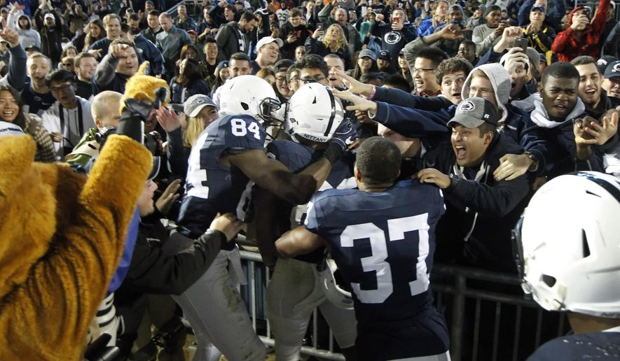 Penn State's Saquon Barkley (26) is mobbed by teammates after scoring the winning touchdown against Minnesota in overtime of an NCAA college football game in State College, Pa., Saturday, Oct. 1, 2016. (AP Photo/Chris Knight)