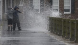 FILE - In this Oct. 3, 2015, a couple takes photos as a wave crashes against a wall along The Battery in Charleston, S.C.  Nearly a year after 2 feet of rain fell on South Carolina, hundreds of people  are still trying to fix their homes.   ( (AP Photo/Chuck Burton)