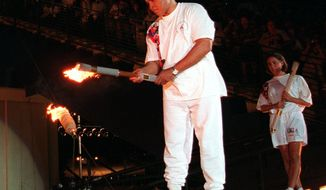 ADVANCE FOR SATURDAY, OCT. 1 - In this July 19, 1996, file photo, American swimmer Janet Evans , right, looks on as Muhammad Ali lights the Olympic flame during the 1996 Summer Olympic Games opening ceremony in Atlanta. Turner Field began its brief life as the main stadium for the 1996 Summer Olympics. After just two decades as the home of the Atlanta Braves, it's headed for another transformation. The Braves are moving to the suburbs next season, leaving the Ted to Georgia State University. (AP Photo/Michael Probst, File)