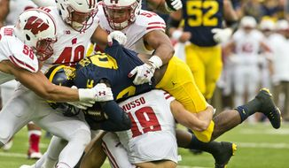 Michigan wide receiver Jehu Chesson, center, is gang-tackled by Wisconsin defenders Zack Baun (56), Jack Cichy (48), T.J. Edwards (53) and Leo Musso (19) in the first quarter of an NCAA college football game at Michigan Stadium in Ann Arbor, Mich., Saturday, Oct. 1, 2016. (AP Photo/Tony Ding)