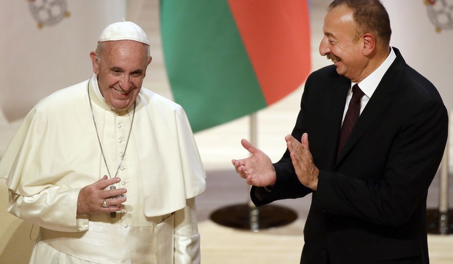 Azerbaijan's President Ilham Aliyev applauds Pope Francis during their meeting at the Heidar Aliyev Centre in Baku, Azerbaijan, Sunday, Oct. 2, 2016. Francis traveled to Azerbaijan on Sunday for a 10-hour visit aimed at encouraging the country's inter-religious harmony while likely overlooking criticism of a referendum that extends the president's term and powers. (AP Photo/Sergei Grits)