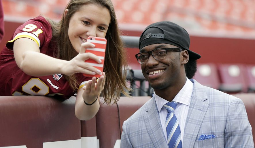 Injured Cleveland Browns quarterback Robert Griffin III takes a selfie with a Washington Redskins fan before an NFL football game Sunday, Oct. 2, 2016, in Landover, Md. (AP Photo/Mark Tenally)