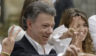 Colombia's President Juan Manuel Santos makes the victory sign after voting in a referendum to decide whether or not to support the peace deal he signed with rebels of the Revolutionary Armed Forces of Colombia, FARC, in Bogota, Colombia, Sunday, Oct. 2, 2016. (AP Photo/Ricardo Mazalan) ** FILE **